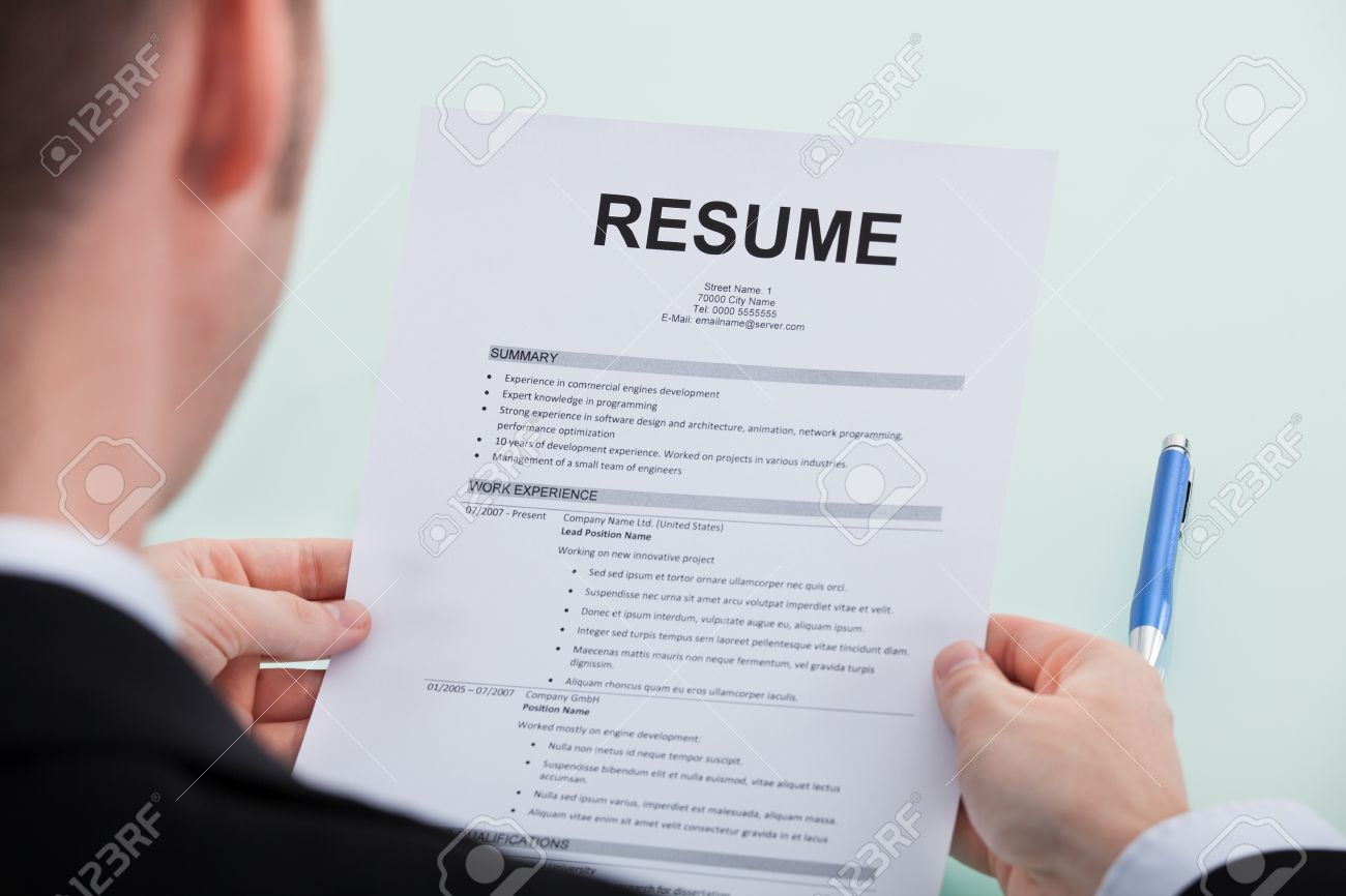 cropped image of businessman reading resume at office desk stock
