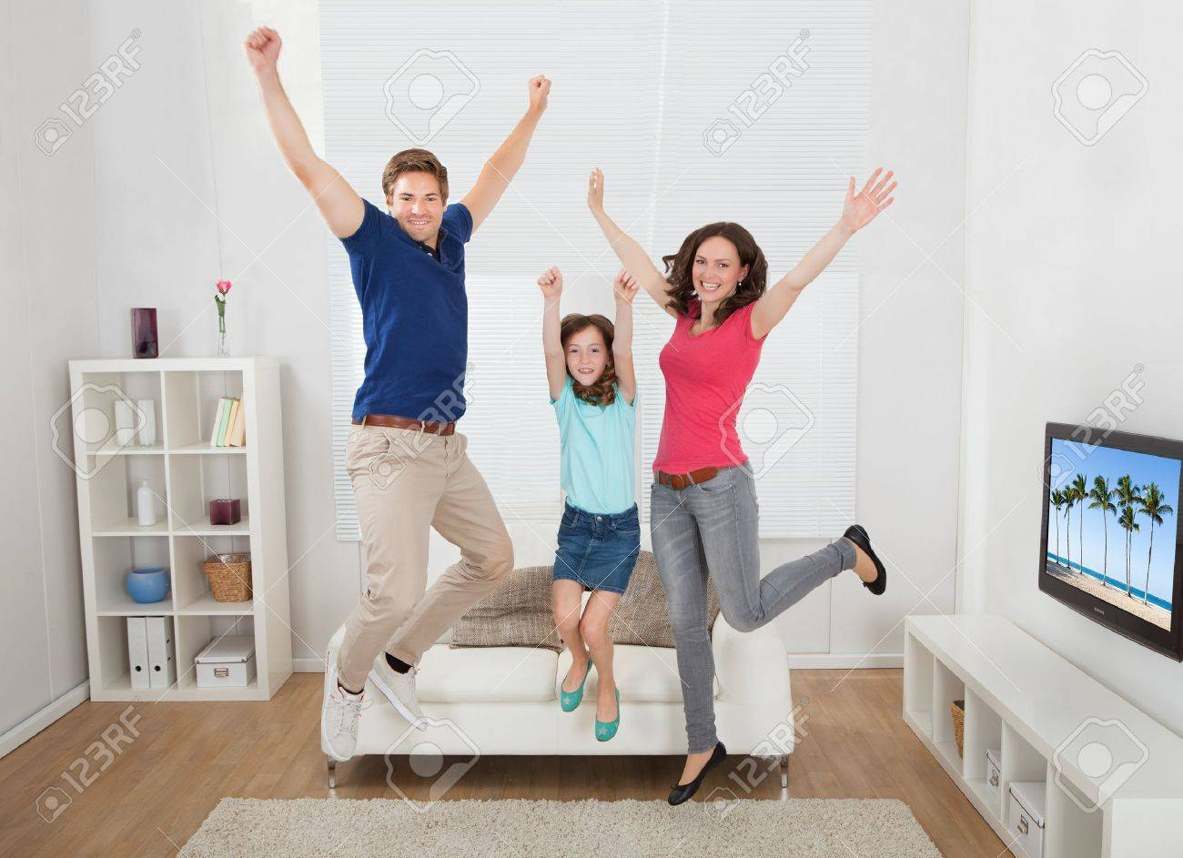 Full Length Portrait Of Excited Family With Arms Raised Jumping ...