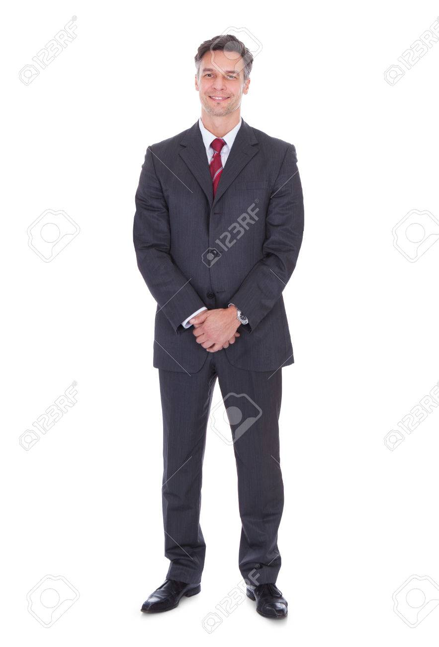 Full length portrait of smiling businessman with hands clasped standing against white background - 33634853