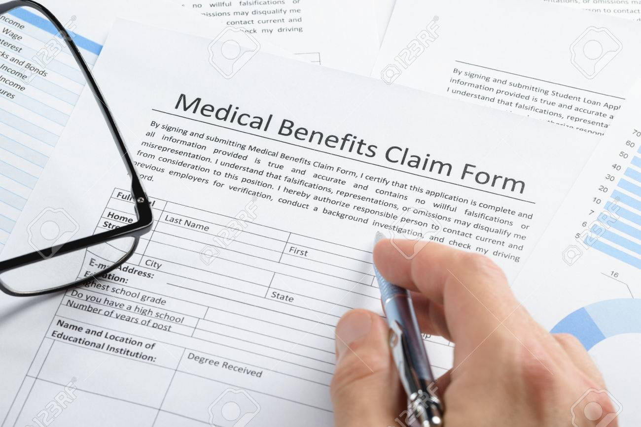 Closeup Of Hand Holding Pen Over Medical Claim Application Form – Medical Claim Form