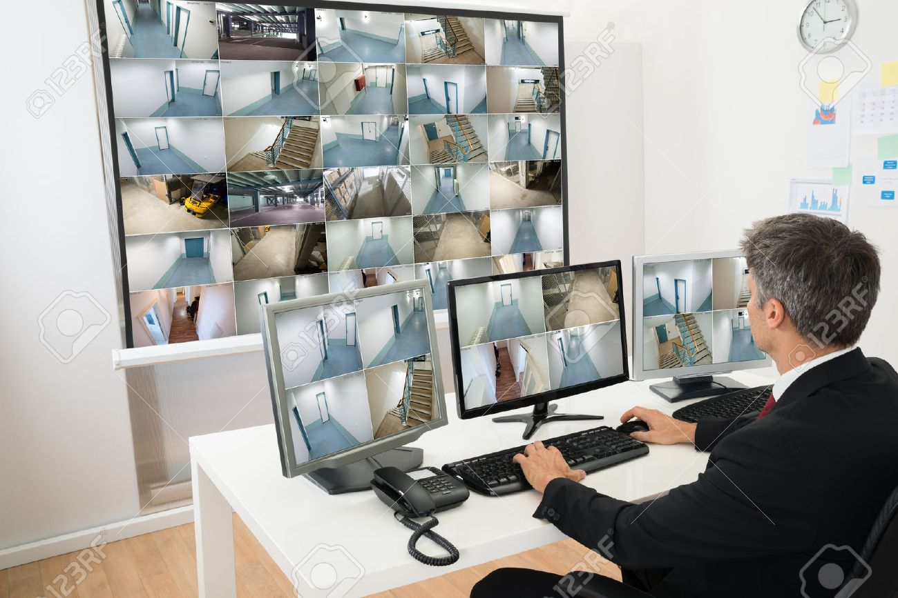 Man In Control Room Monitoring Multiple Cctv Footage - 35462224