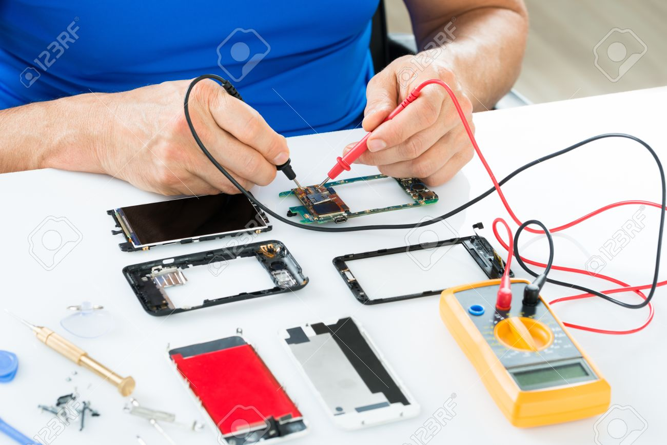 close up of man repairing cellphone with multimeter stock photo