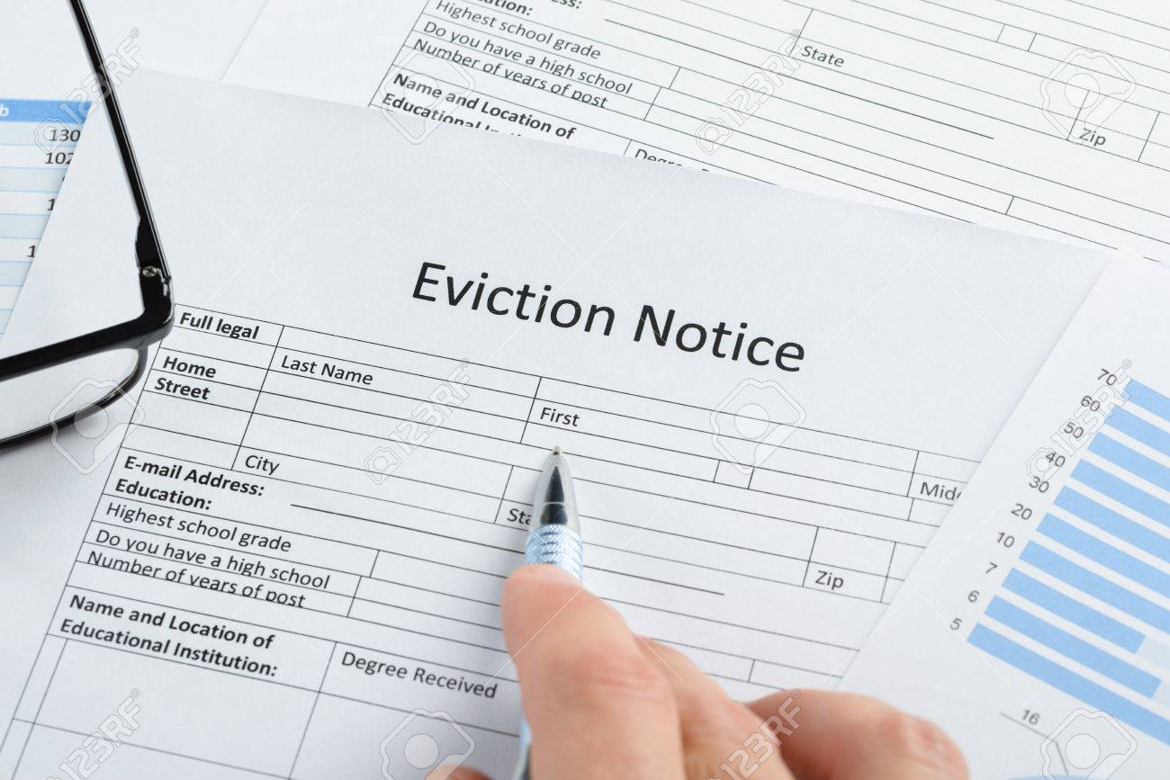 close up of hand with pen and eyeglasses over eviction notice