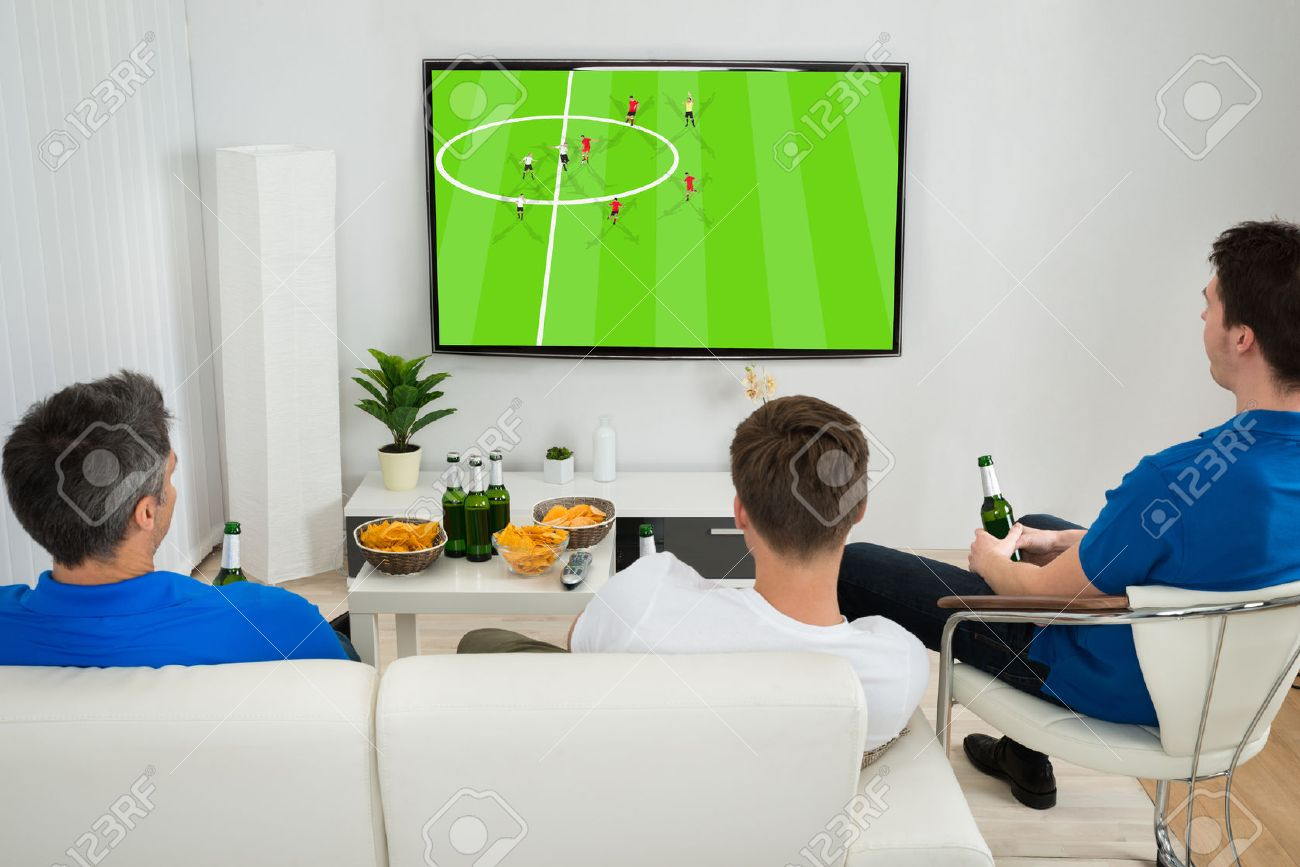 Three Men Sitting On Couch Watching Football Match On Television  # Modele De Table Television
