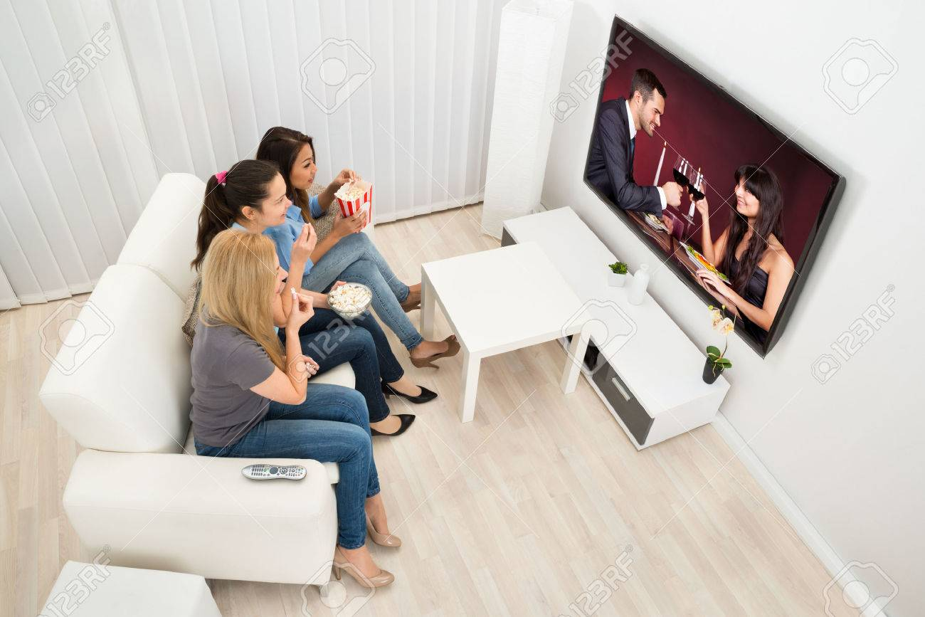 Multiethnic Young Women Sitting On Couch Watching Movie At Home - 36498085
