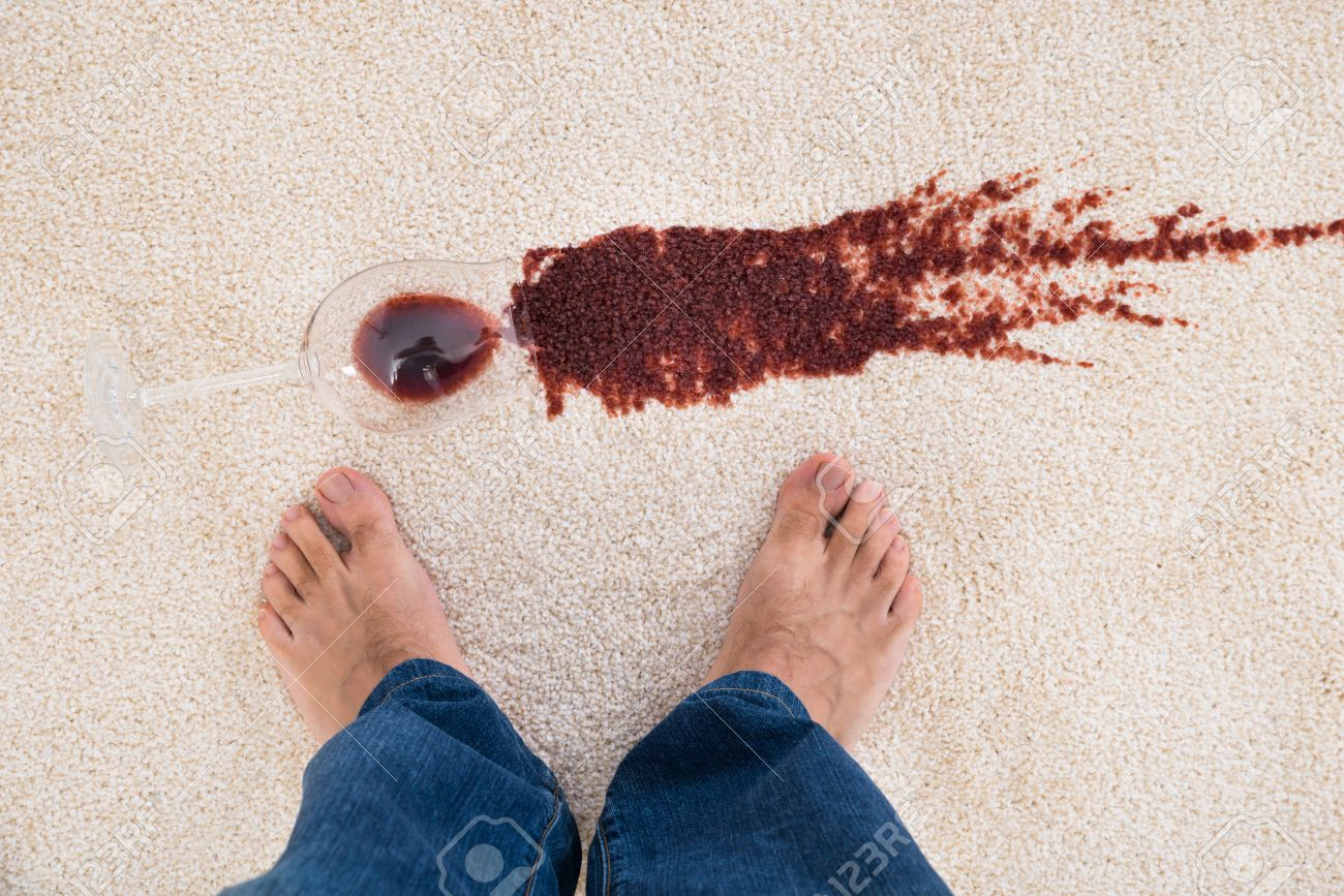closeup of a feet standing near red wine spilled on carpet stock photo