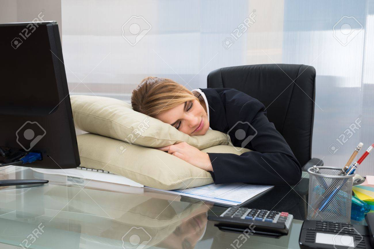 Young Businesswoman Sleeping On Pillow At Desk In Office