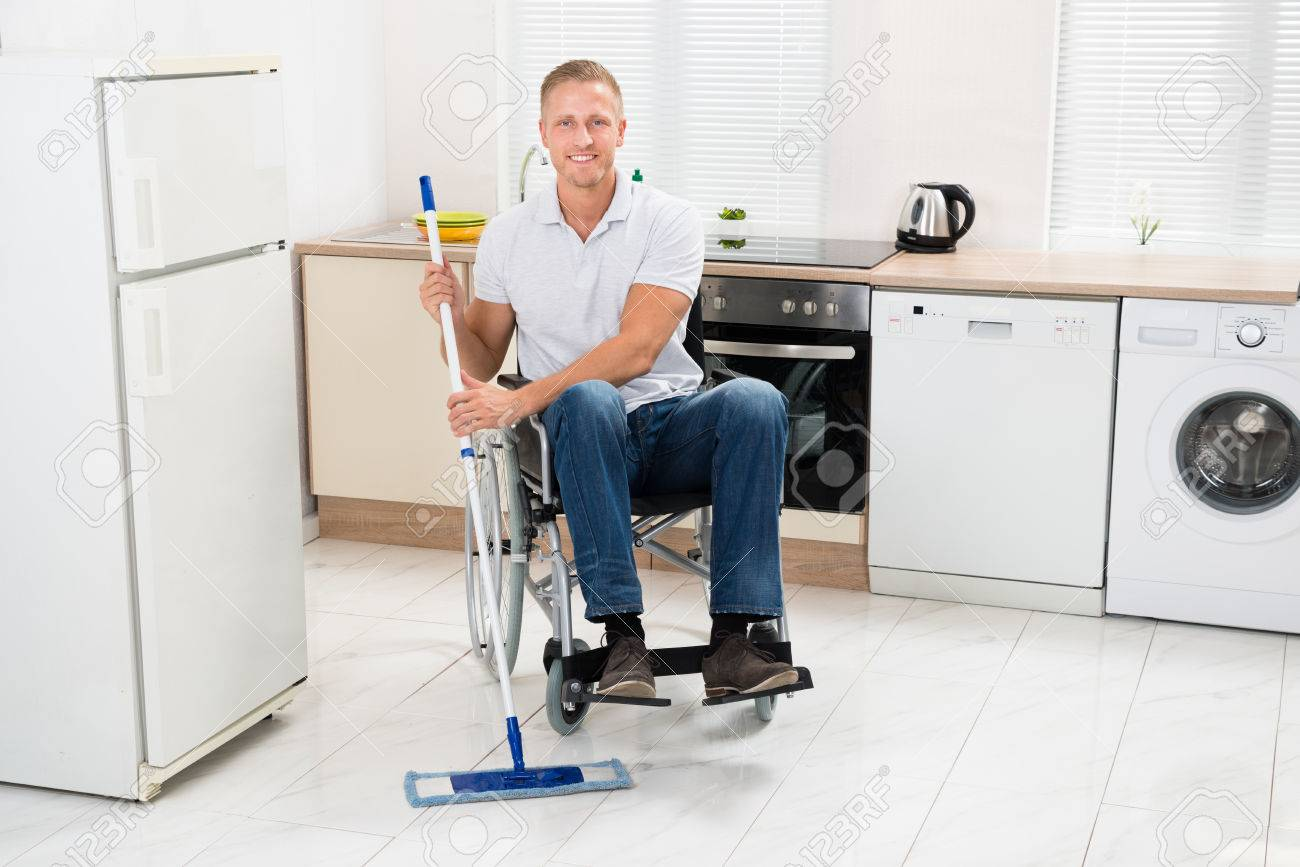 Mopping Kitchen Floor Young Happy Handicapped Man On Wheelchair Mopping Floor In Kitchen