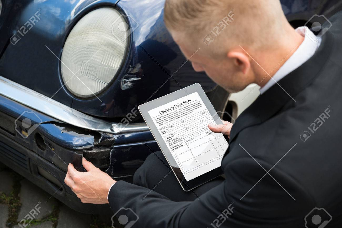 Insurance Agent Inspecting Damaged Car With Insurance Claim Form ...