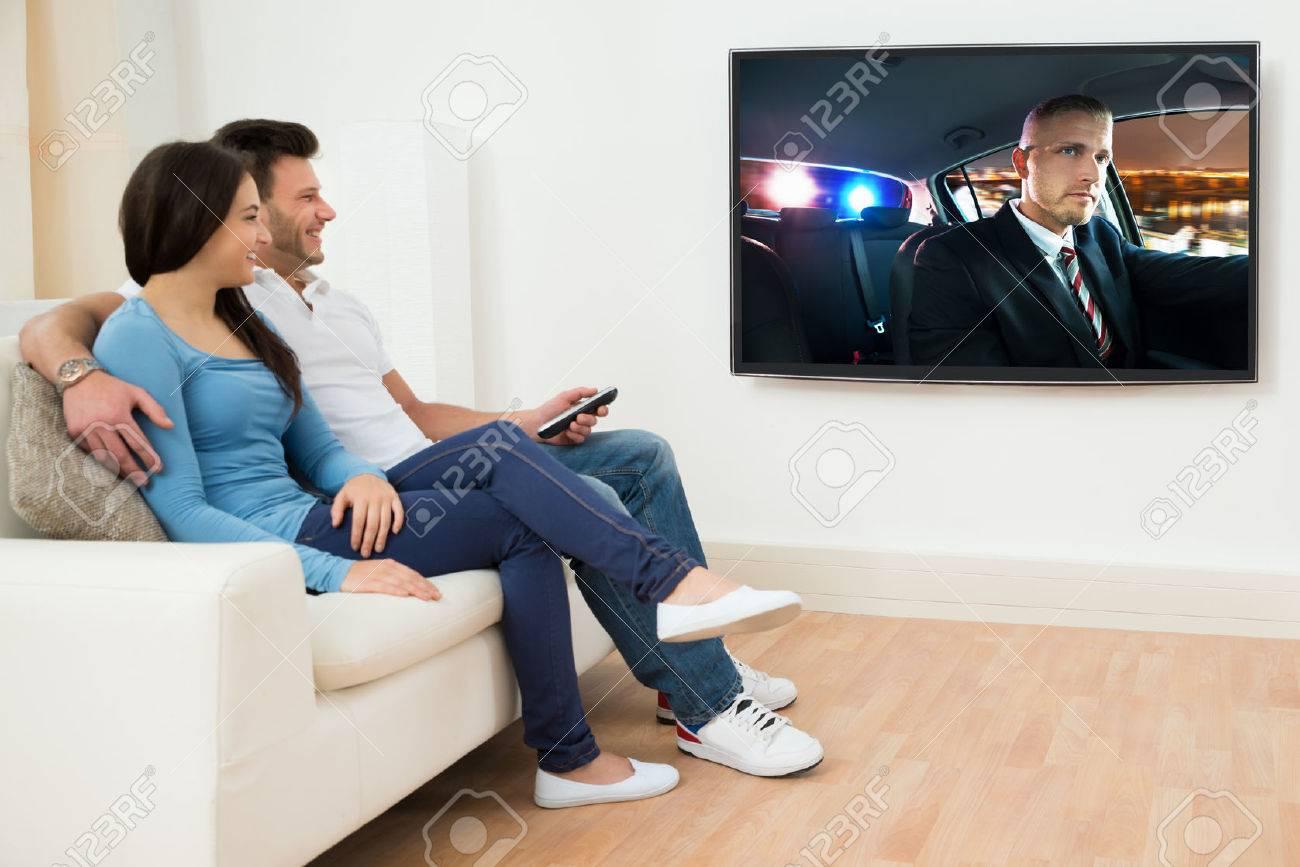 Glückliche Junge Paare Im Wohnzimmer Sitzt Auf Couch Film ...