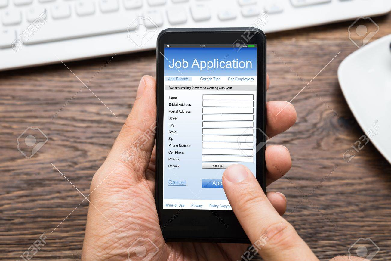 close up of person hands filling online job application on mobile close up of person hands filling online job application on mobile phone at desk stock