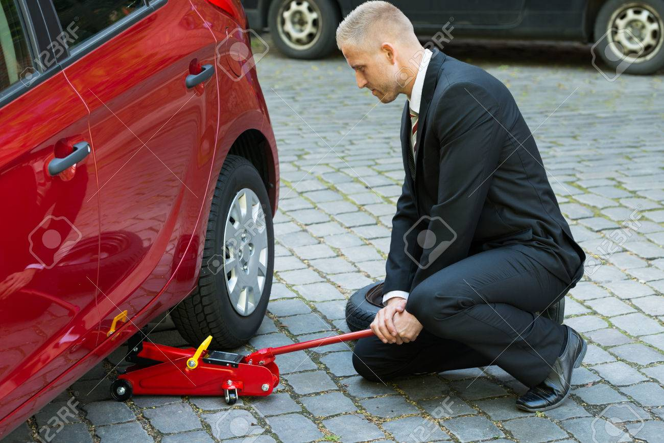 Man Trying To Lift The Car With Red Hydraulic Floor Jack For