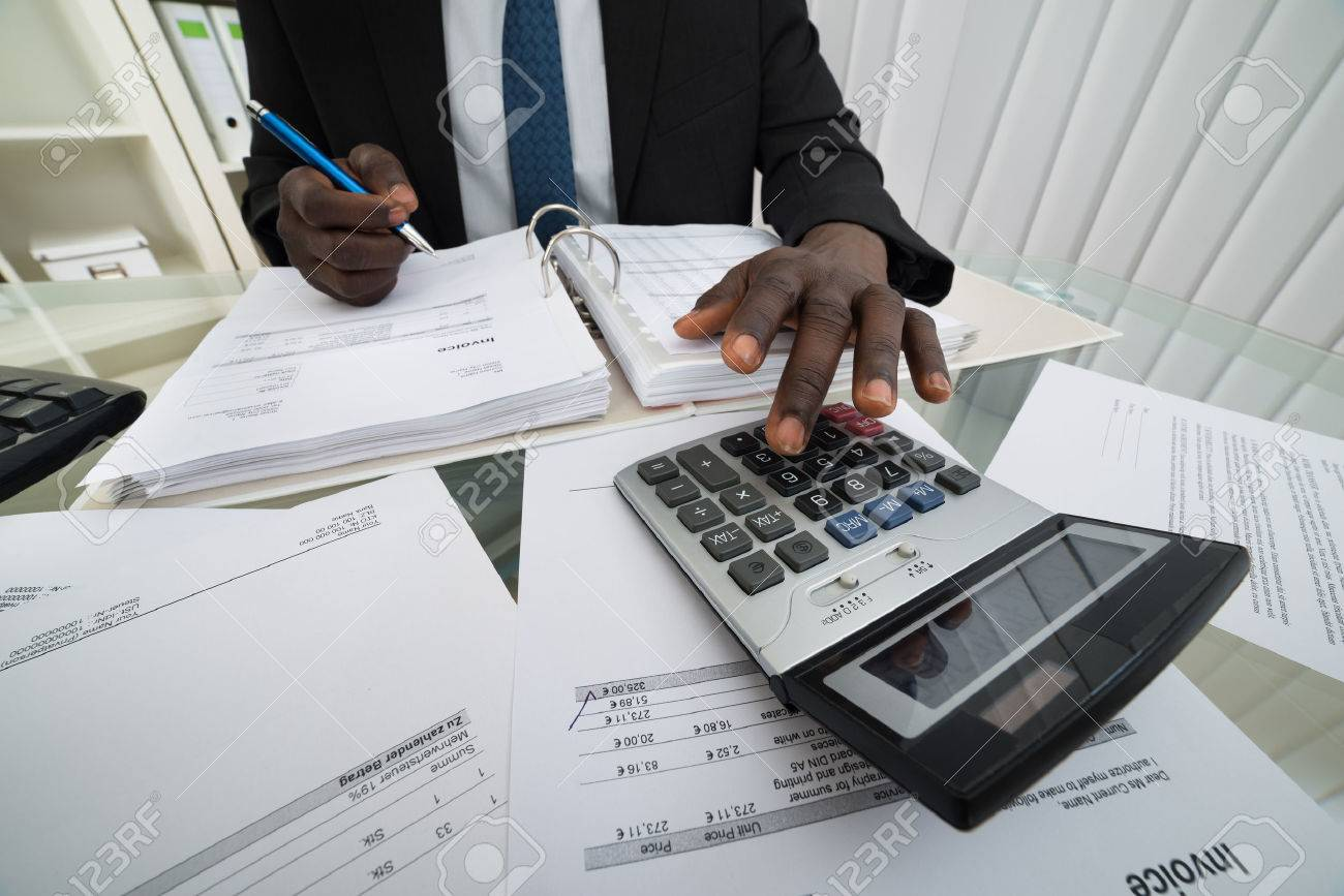 close up of businessman calculating invoices using calculator close up of businessman calculating invoices using calculator stock photo 41933873