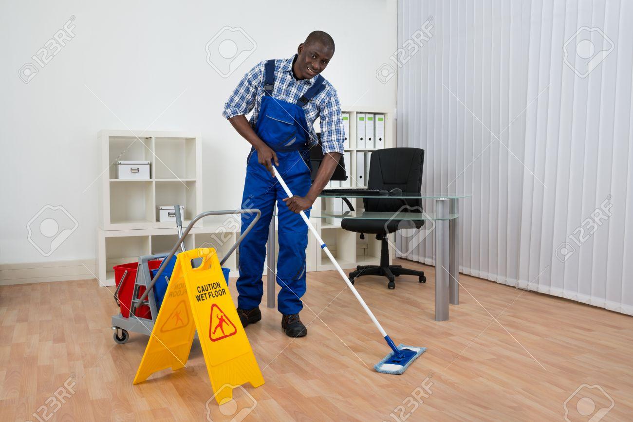 Fußboden Reinigen ~ Junge glückliche hausmeister reinigung fußboden mit wet floor
