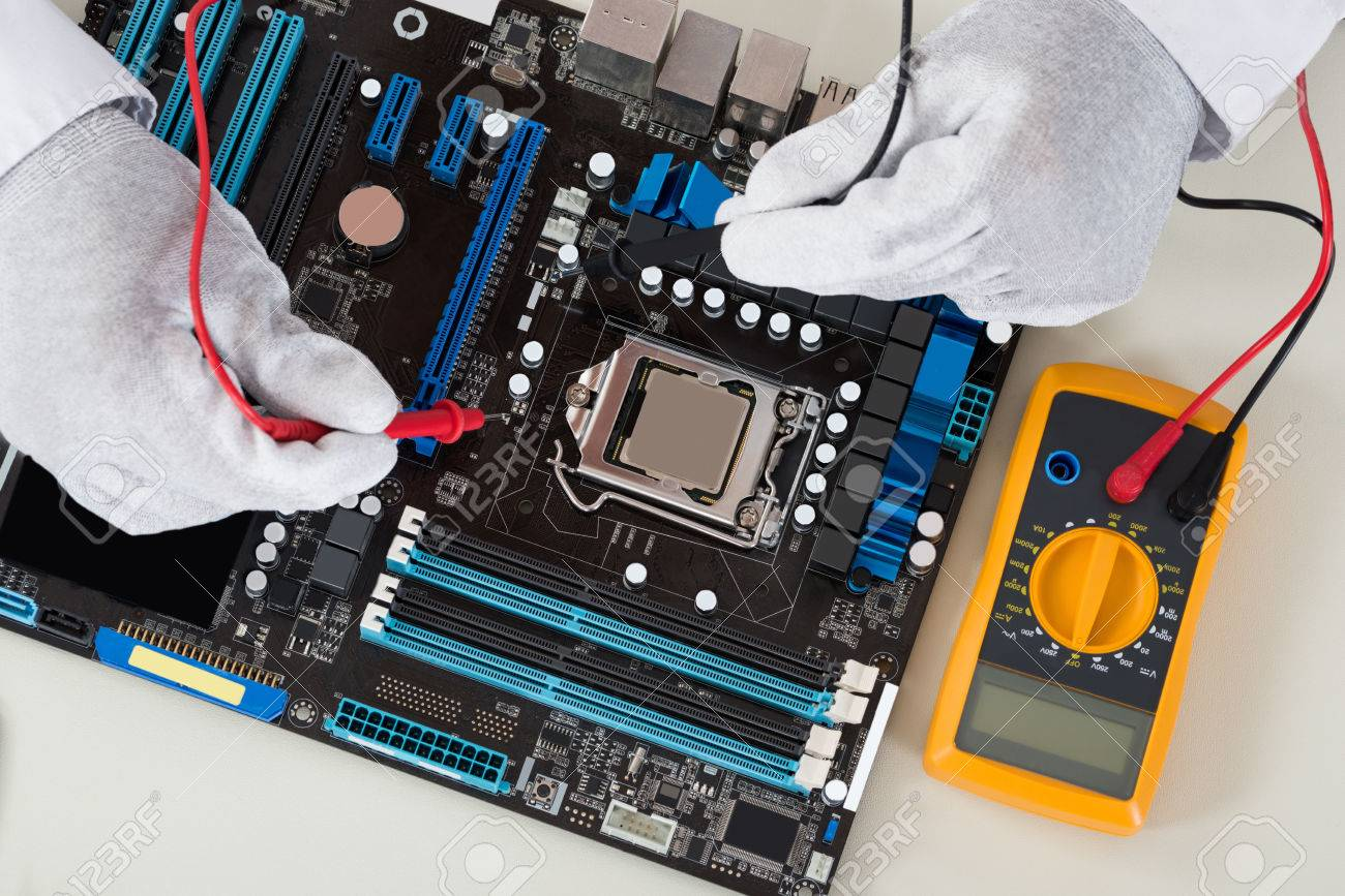 close up of person hands checking motherboard with multimeter stock