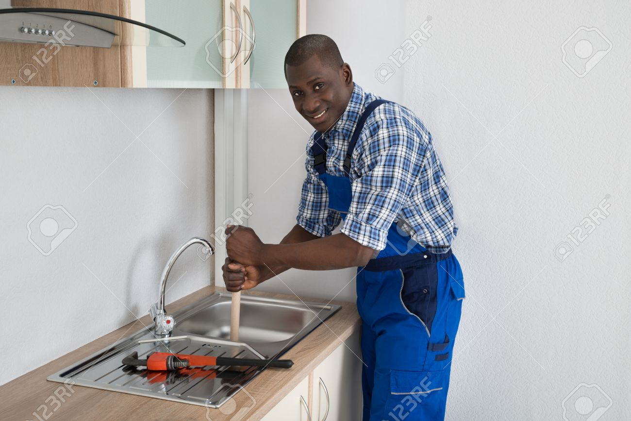 42197352 Young Happy African Plumber Using Plunger To Unclog Kitchen Sink Stock Photo