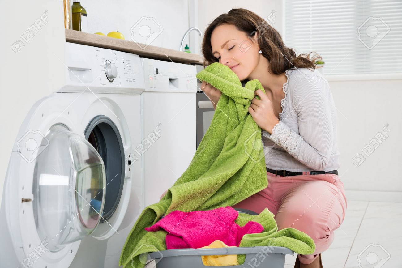 Young Woman Crouching With Cleaned Clothes Near The Electronic Washer - 43082611