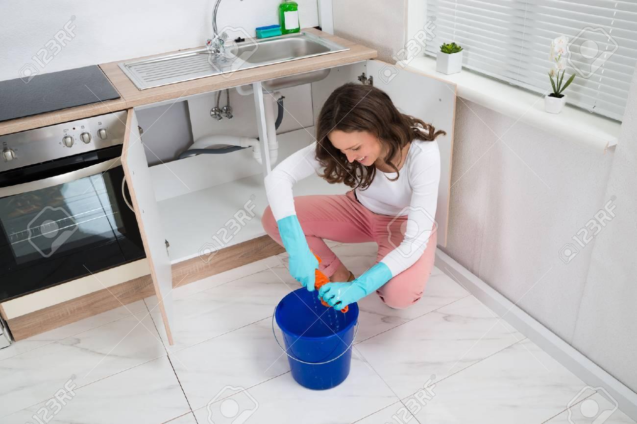 Junge Frau Drückte Nassen Lappen In Blue Bucket In Küche Zimmer  Standard Bild   43083035
