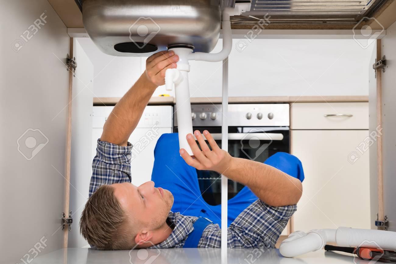 Fußboden Reparieren ~ Männlich plumber auf fußboden liegt beim reparieren rohr in den