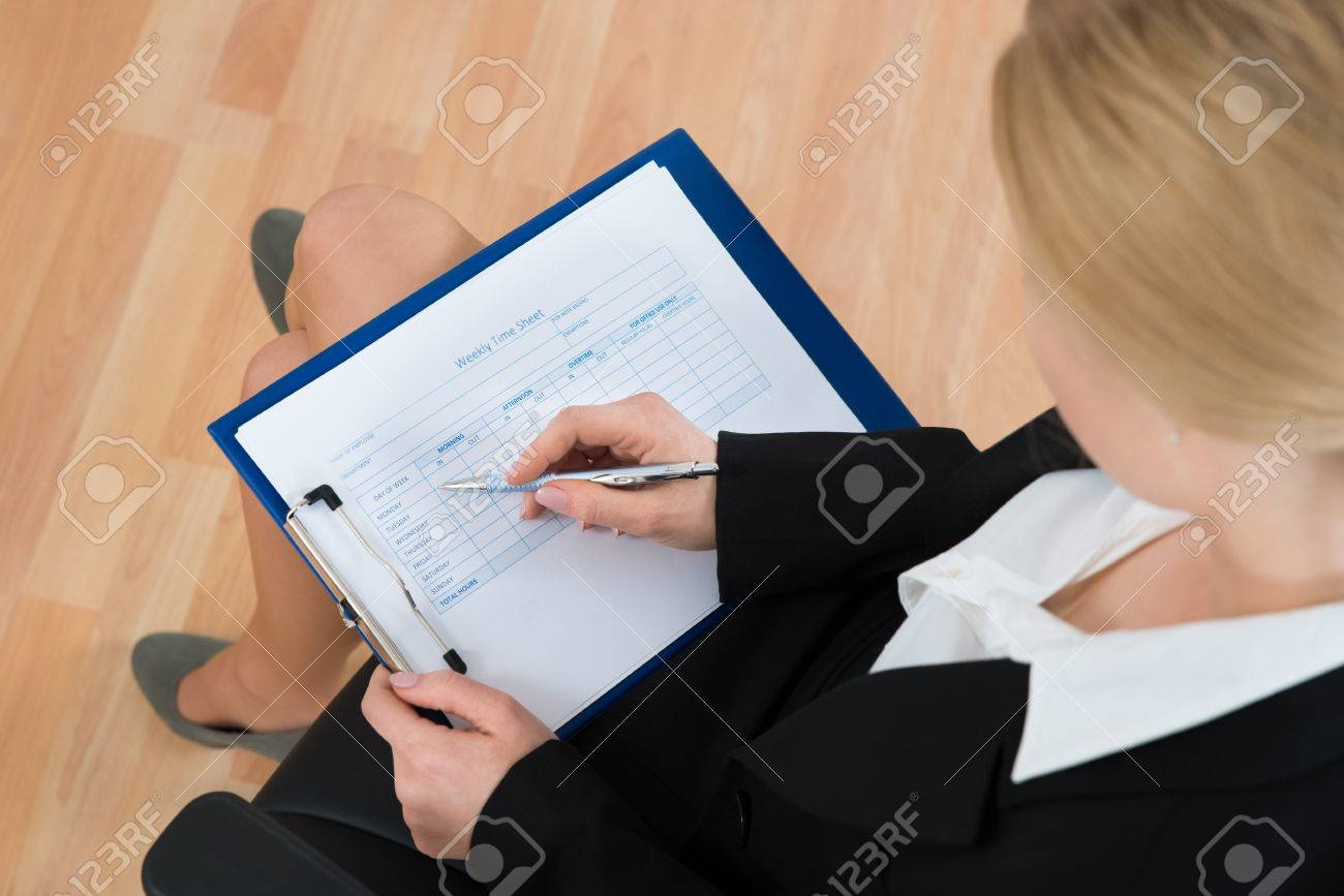 high angle view of businesswoman filling blank weekly time sheet