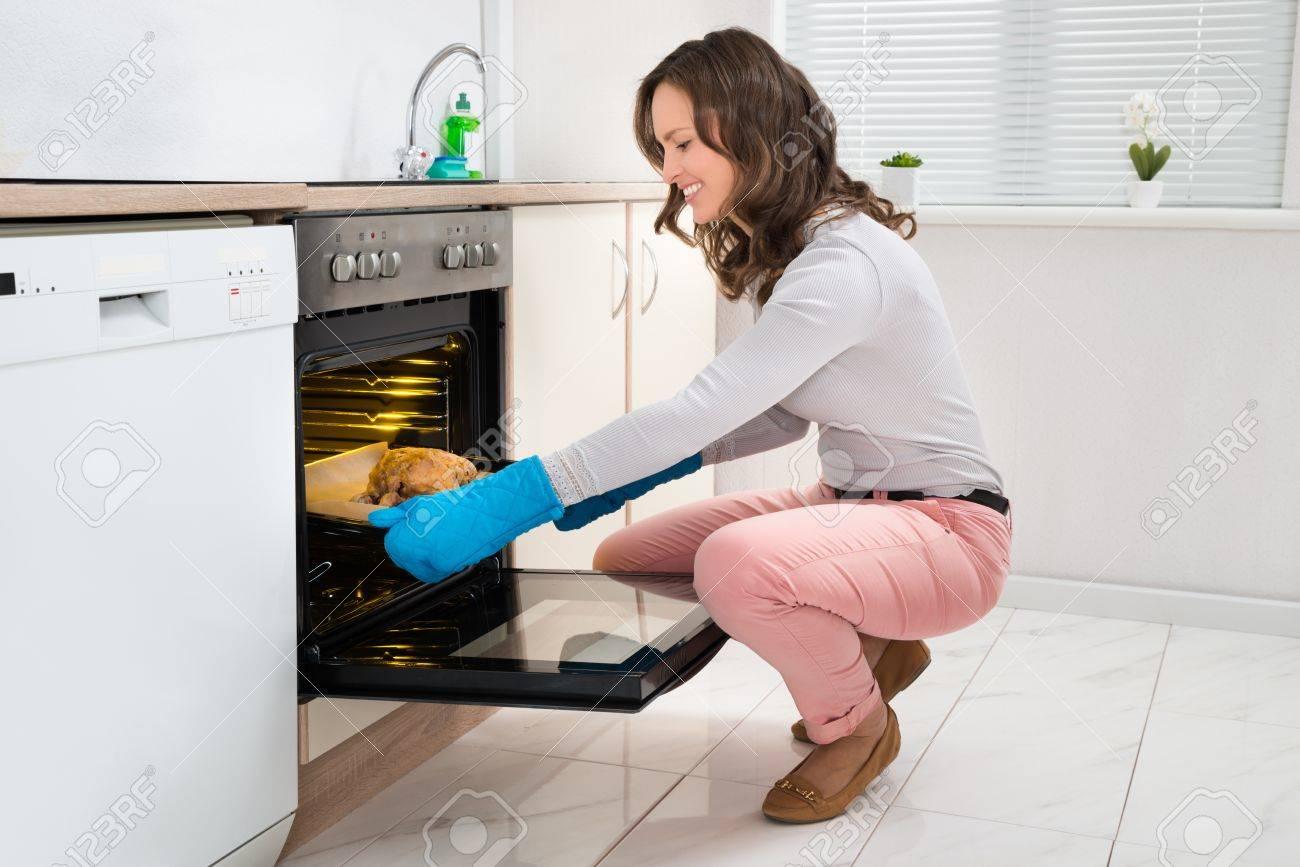 Schöne öfen schöne junge frau trägt handschuhe kochen huhn in ofen lizenzfreie