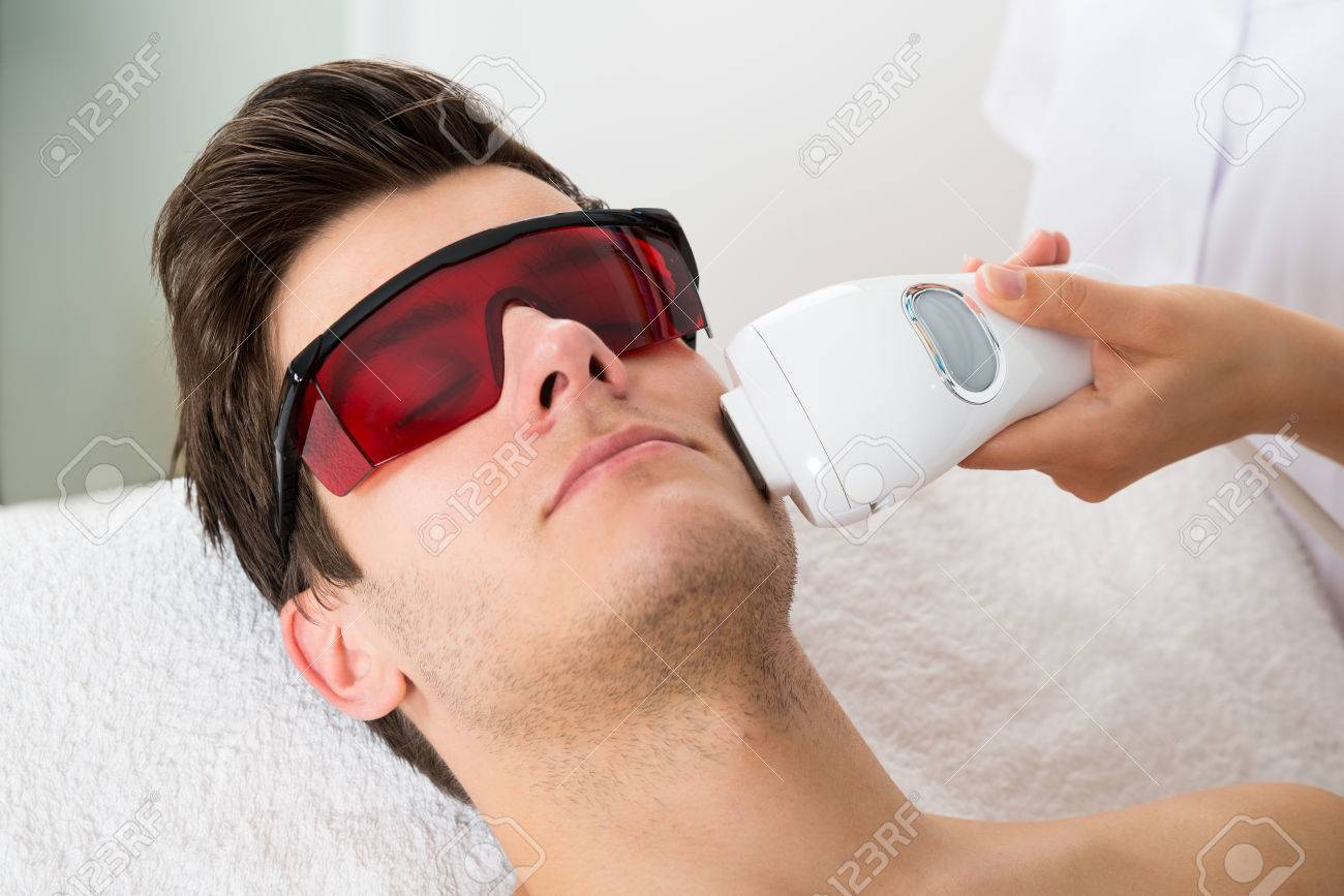 Young Man Receiving Laser Hair Removal Treatment At Beauty Center - Laser hair removal face