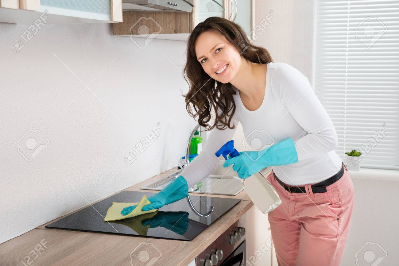 Young Woman Smiling While Cleaning Induction Hob On Countertop At Home - 43694017