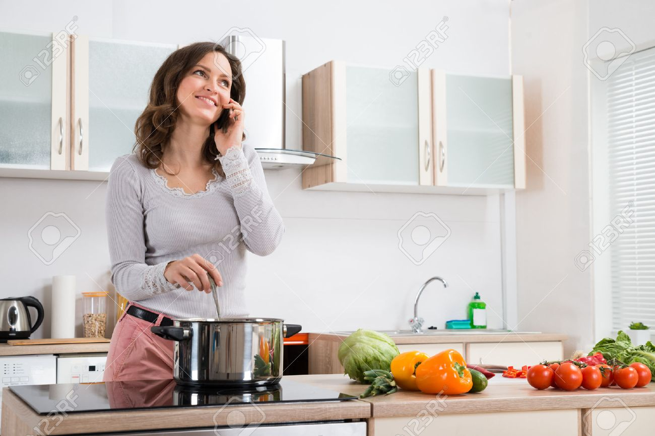 happy woman talking on mobile phone while cooking in kitchen stock