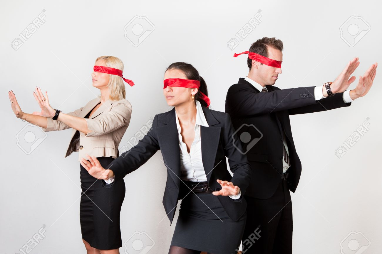 2d239b46c99 Group of disoriented businesspeople with red ribbons on eyes Stock Photo