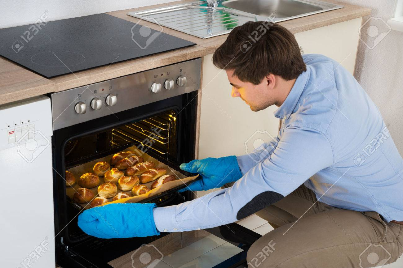 Young Man Taking Baking Tray With Baked Bread From Oven In Kitchen - 44714119