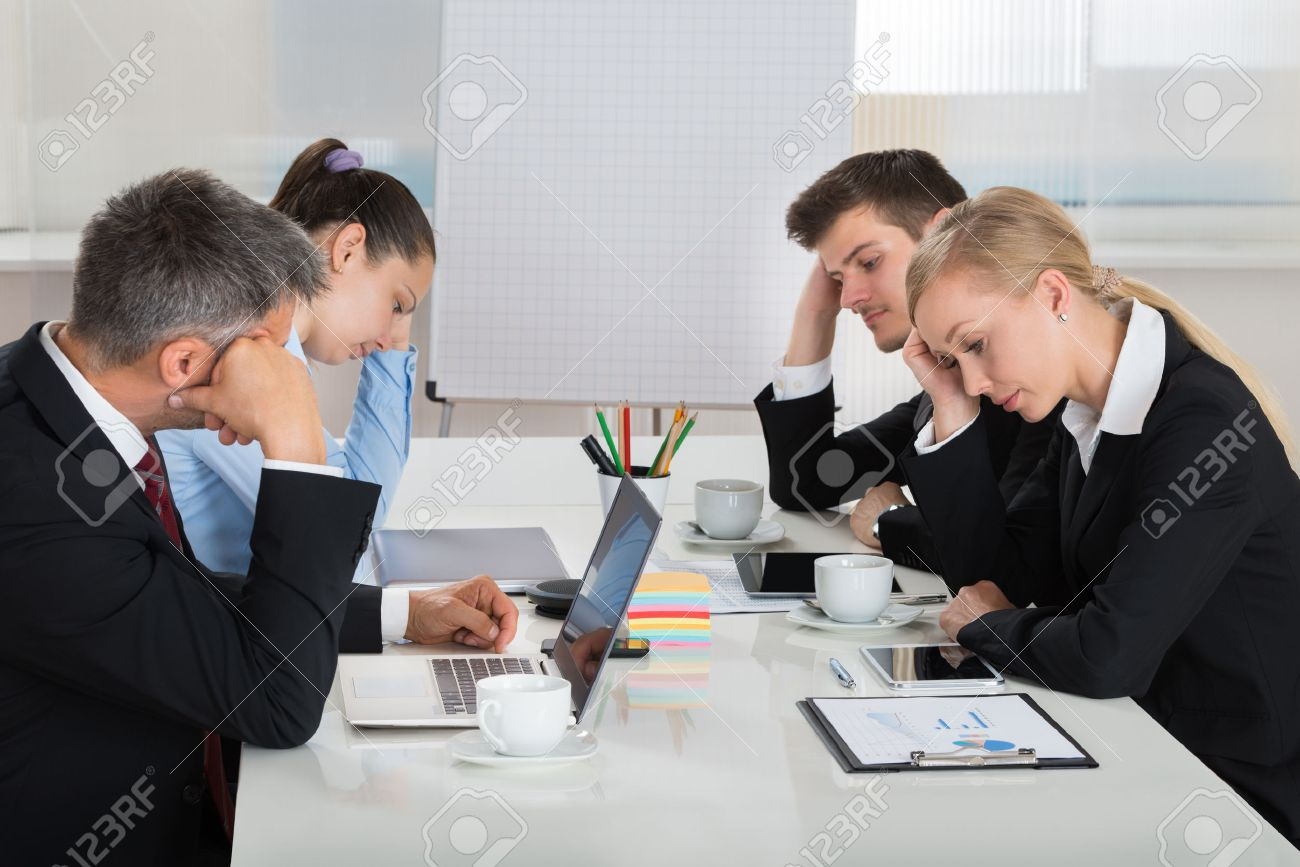 team of unhappy businesspeople sitting in business meeting stock stock photo team of unhappy businesspeople sitting in business meeting
