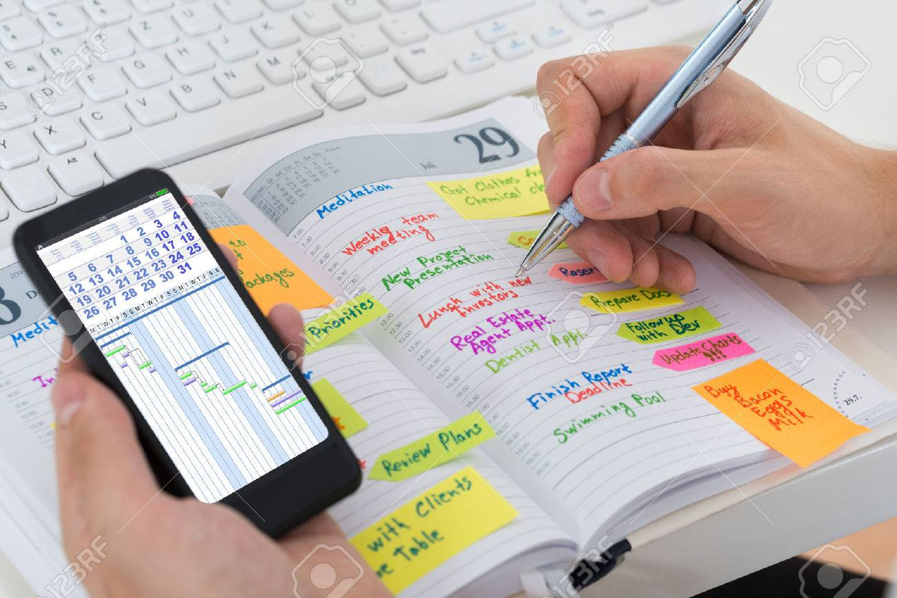 Close-up Of Person Hands With Mobile Phone And List Of Work In Diary - 46081176