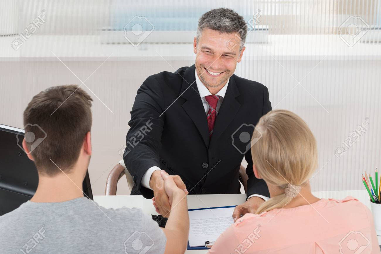 Mature Male Agent Shaking Hands With Man In Office - 46081229