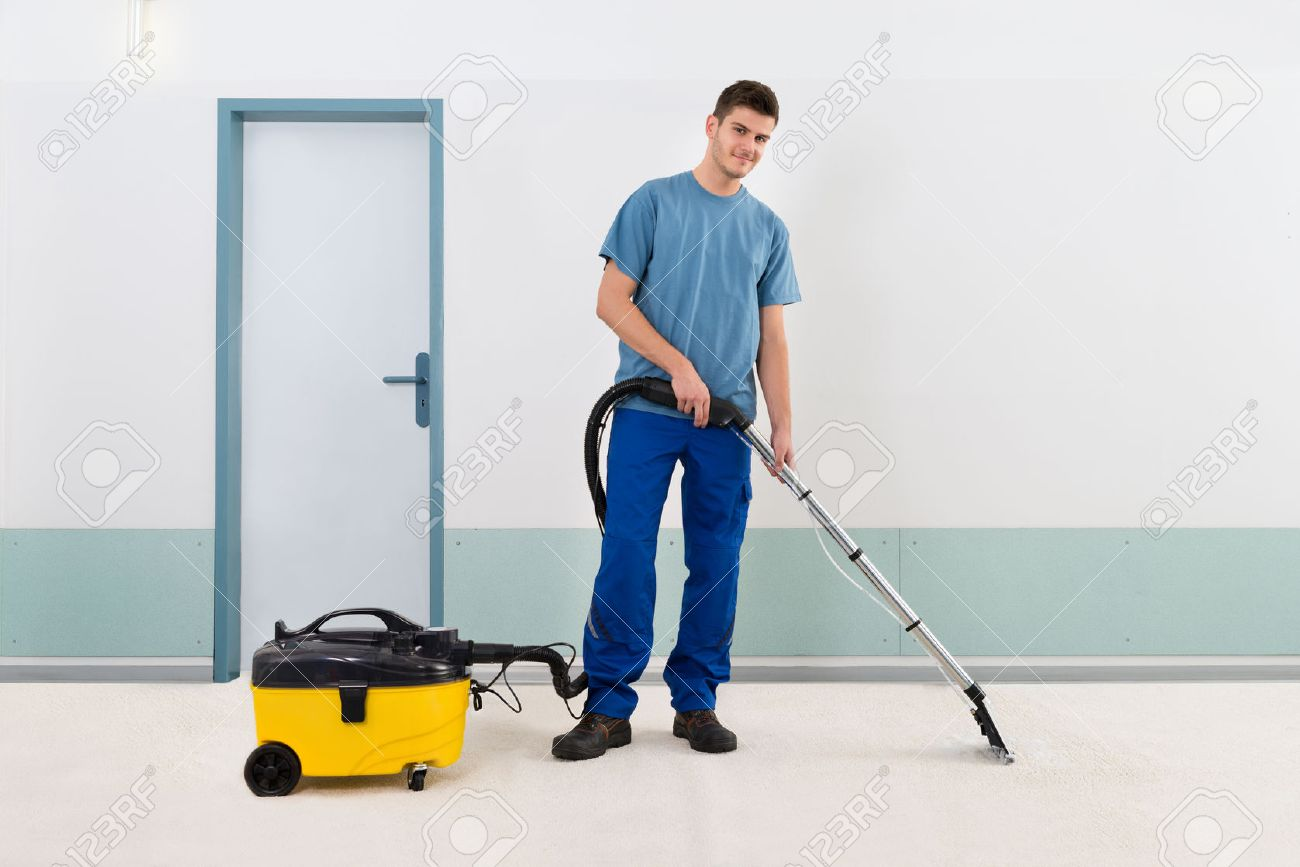 young male cleaner in uniform vacuuming floor stock photo picture