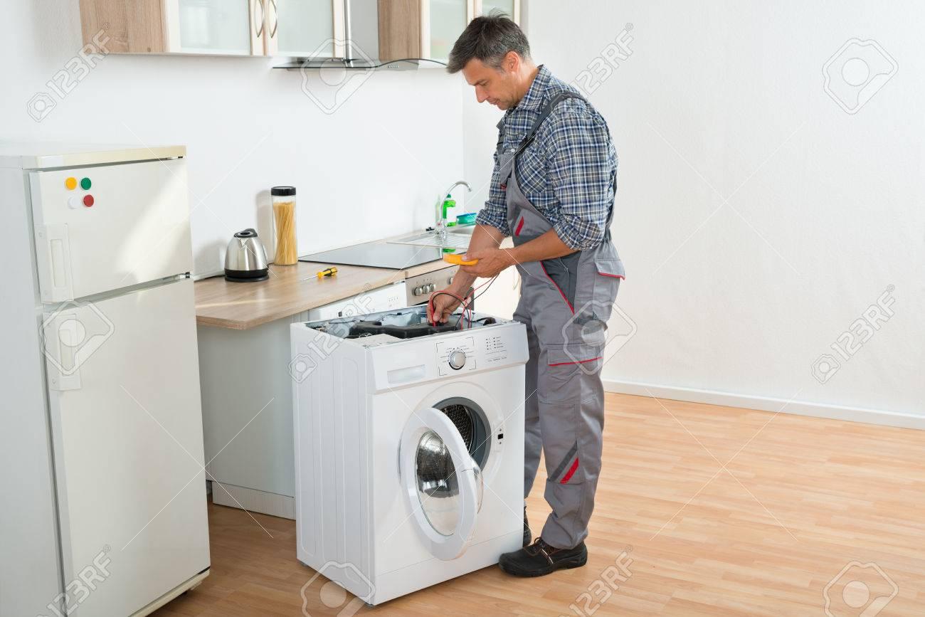 デジタルマルチメータとキッチンに洗濯機をチェック技術者の全長