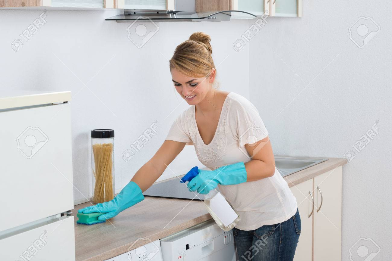 Stock Photo   Young Woman Cleaning Kitchen Counter With Sponge At Home