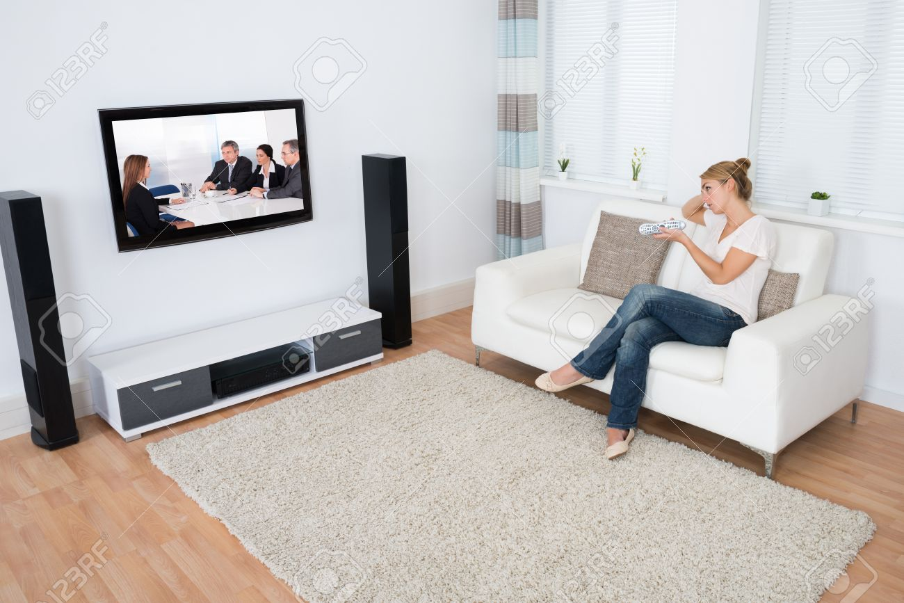 Full Length Of Young Woman Watching TV While Sitting On Sofa.. Stock ...