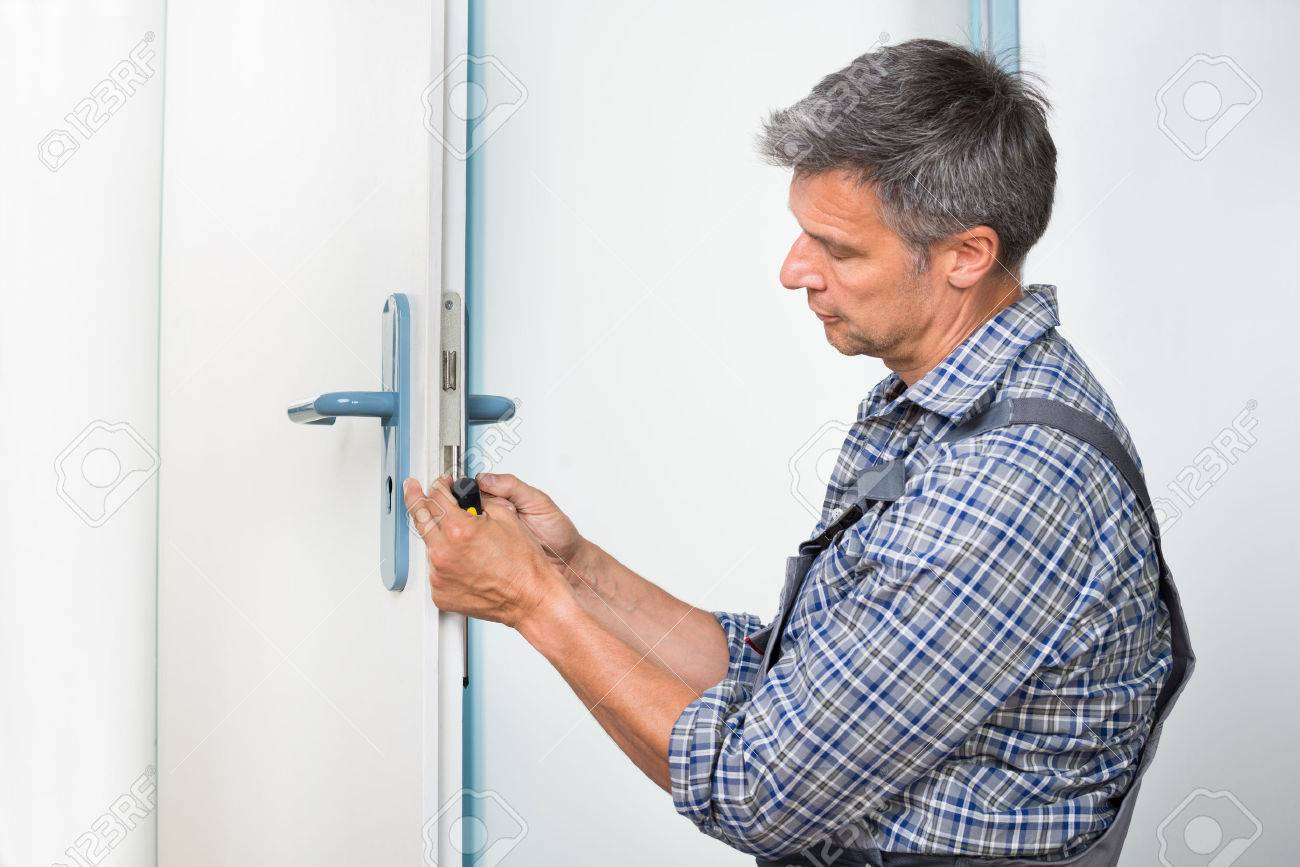 Male carpenter fixing lock in door with screwdriver at home Stock Photo - 47883872