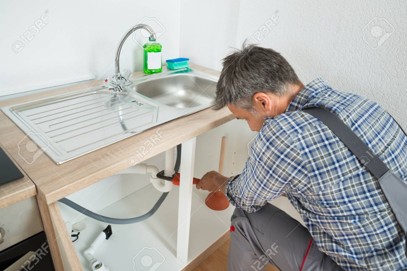 Male Plumber Fixing Sink Pipe With Adjustable Wrench In Kitchen ...