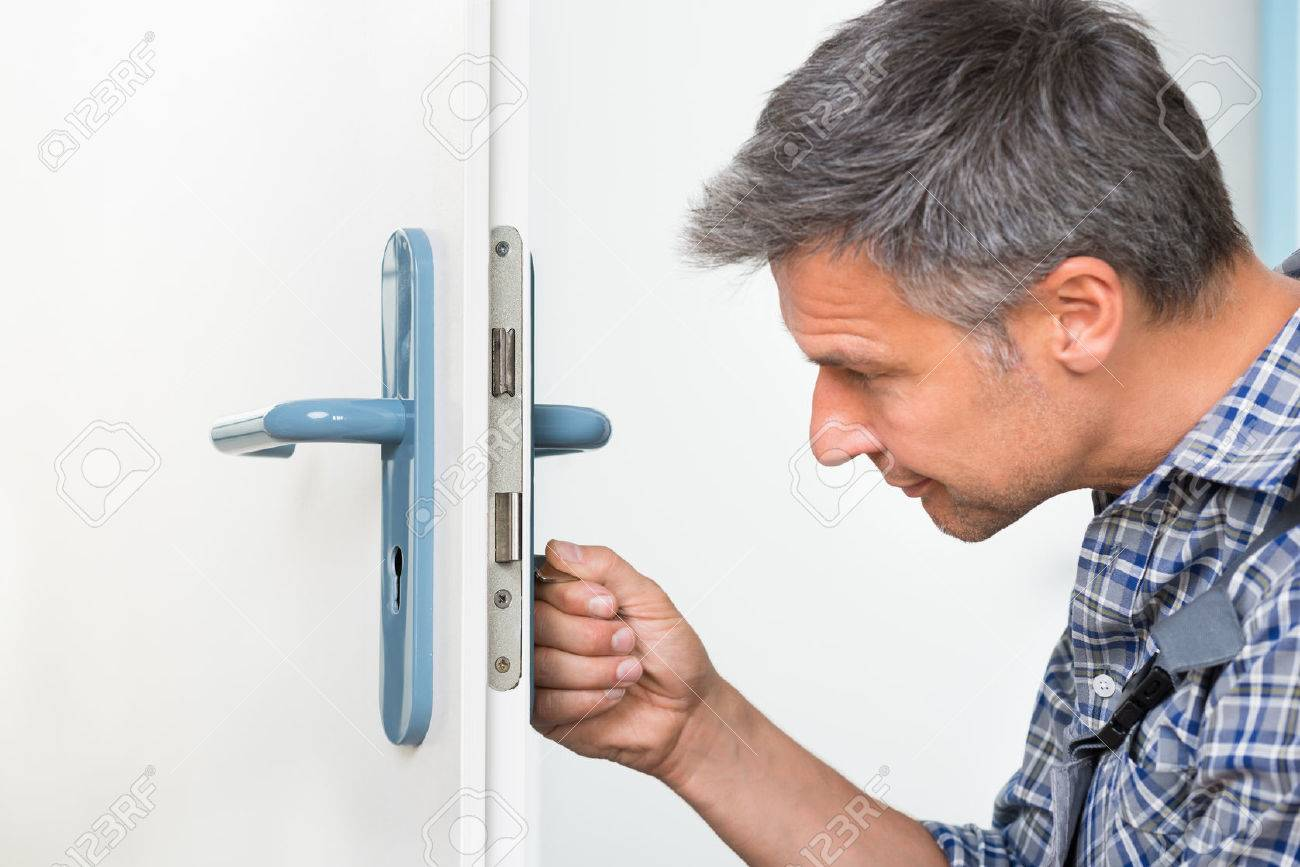 Male carpenter fixing lock in door with screwdriver at home Stock Photo - 48227062