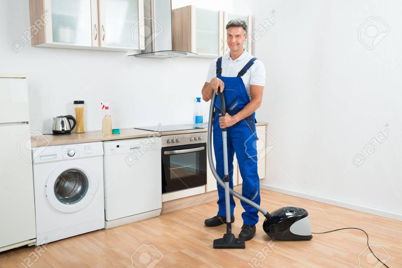 Volledige lengte portret van mannelijke conciërge reinigen vloer