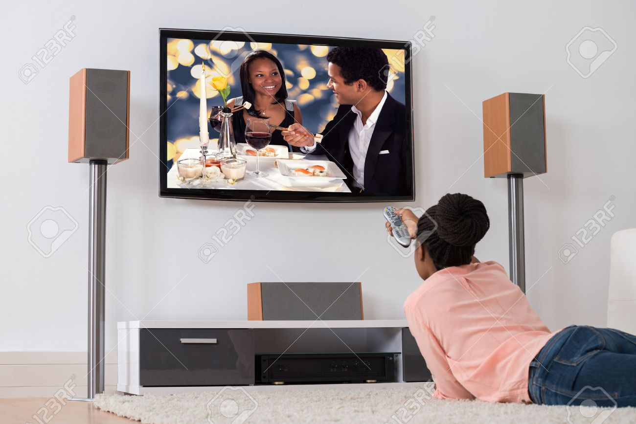 Young African Woman Lying On Carpet Watching Television - 50244321