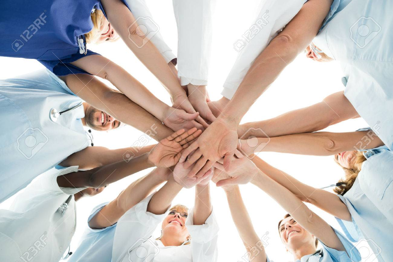 Directly below shot of multiethnic medical team stacking hands over white background - 50244730
