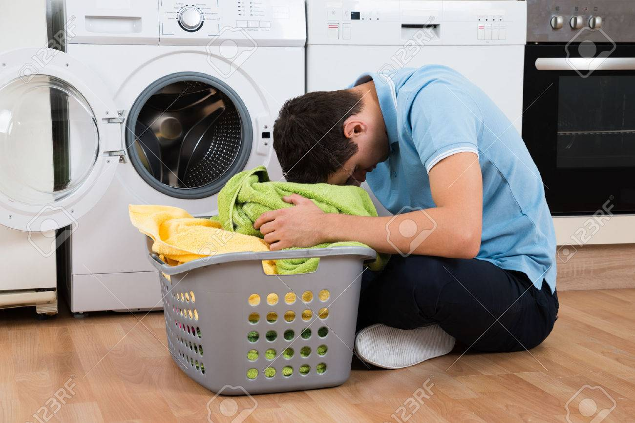 Exhausted young man with laundry basket sitting on floor by washing machine at home - 50245009