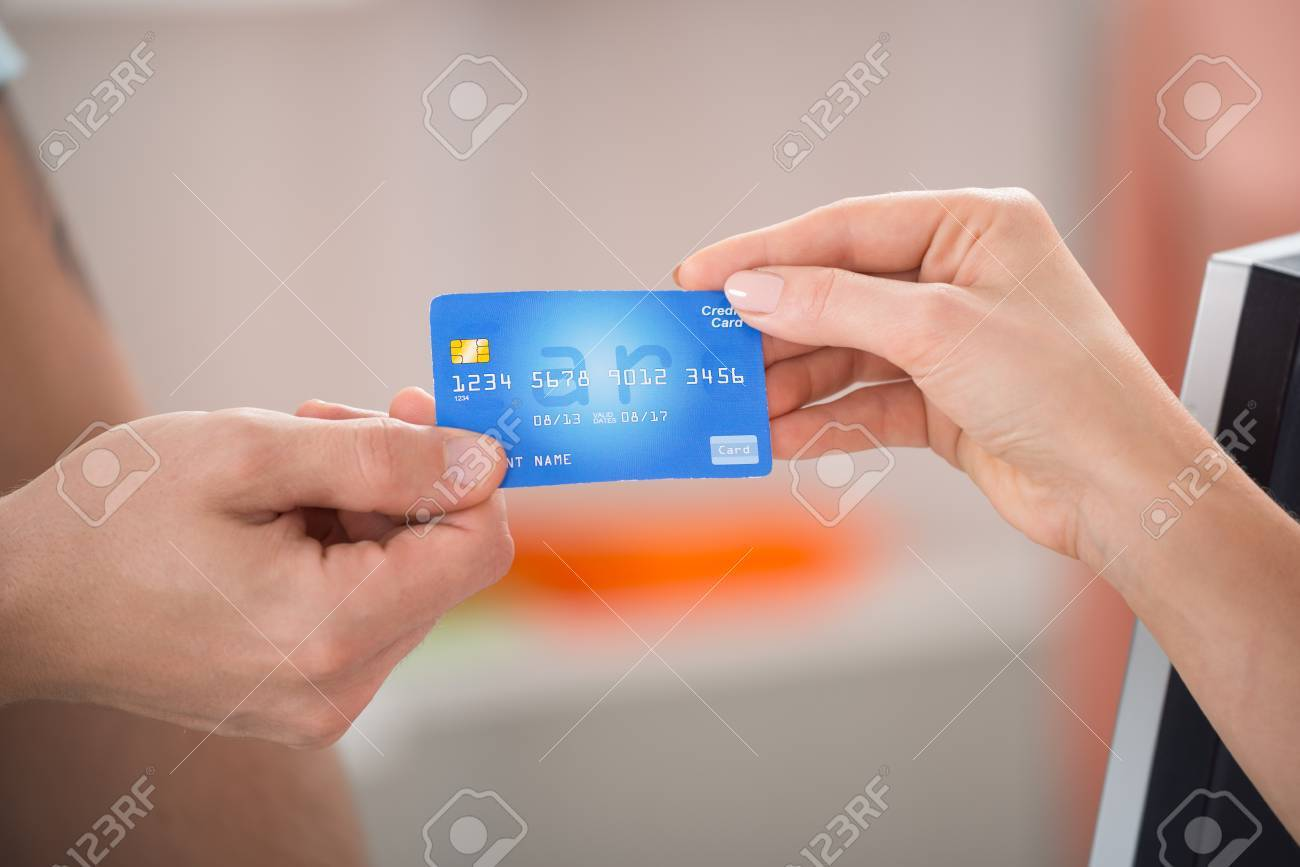 Cropped Image Of Salesman Taking Credit Card From Female Customer