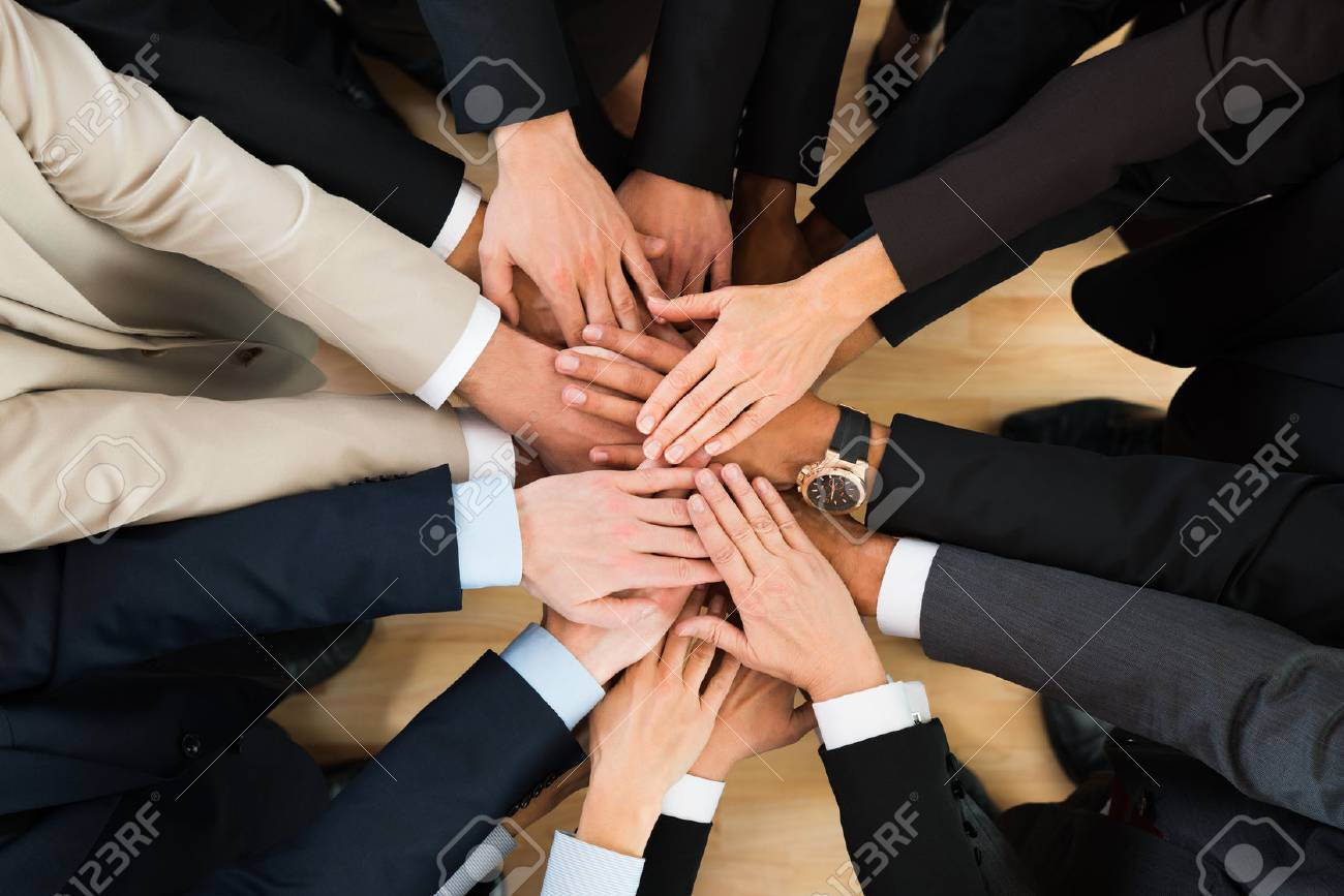 Directly above shot of business team stacking hands in office - 50245434