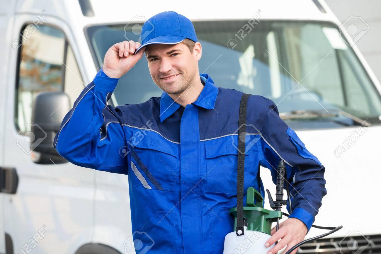 Portrait of confident pest control worker wearing cap against truck - 50278198