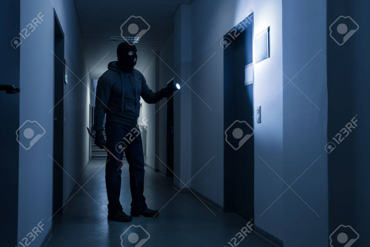 Full length of burglar with flashlight and crowbar in dark office building - 50691198