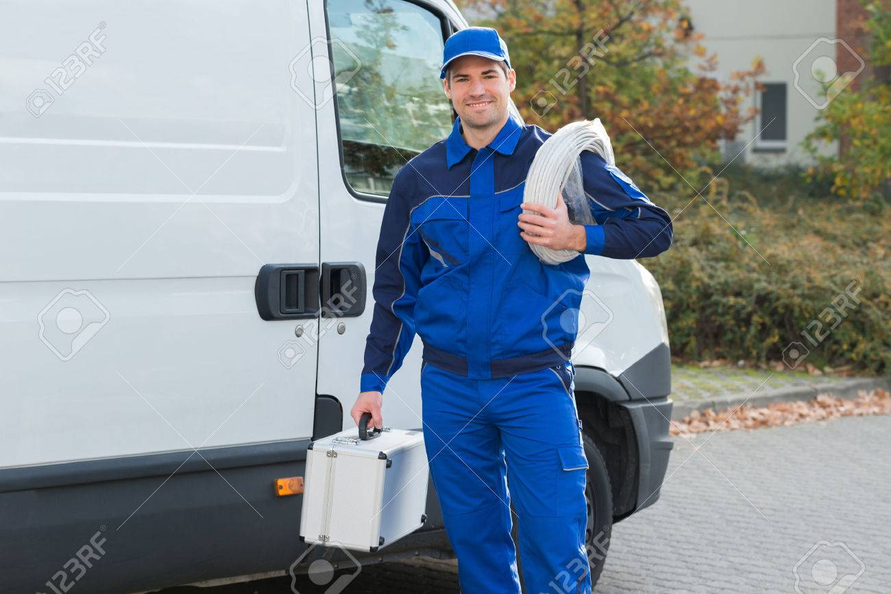 Portrait of confident electrician with cable coil and toolbox standing outside truck - 50692387