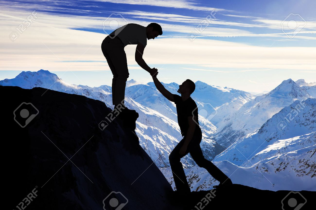 Silhouette young man assisting male friend in climbing rock - 50692518